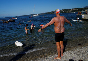Swimmers Gewert, Naunton and Whitehead celebrate after swiming a 70 km relay across Lake Leman at Bains des Paquis in Geneva
