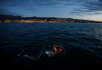 Whitehead swims at sunset during a 70 km relay across Lake Leman from Montreux to Geneva near Evian-les-Bains
