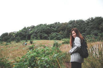 A beautiful Asian woman tourist walking and trekking along the mountains in tropical forest with feeling happy