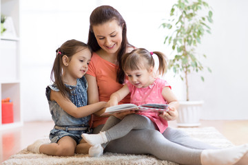pretty mother reading book to her daughters