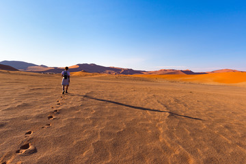Tourist walking on the sand dunes at Sossusvlei, Namib desert, Namib Naukluft National Park, Namibia. Traveling people, adventure and vacations in Africa.