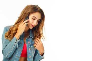 Young happy woman with curly hair is talking on the phone over white background