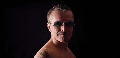 portrait of a man with tattoo and sunglasses and black background