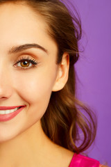portrait of half face of beautiful woman with beautiful makeup looking at camera