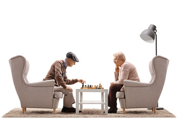 Elderly man and an elderly woman seated in armchairs playing a game of chess