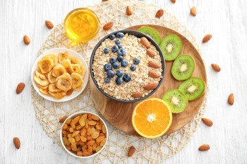 Composition with oatmeal flakes and many different toppings on wooden background
