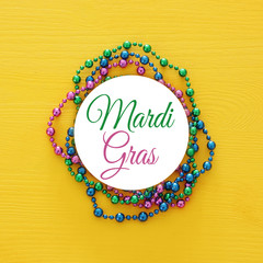 Top view image of colorful beads with text MARDI GRAS. Flat lay.