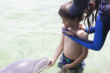 Vacation Lifestyle -Happy Boy hugging a dolphin