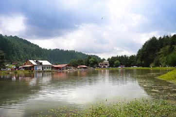 una cabaña en medio de un gran bosque, con un lago en frente. Lugar perfecto para usar la tiroleza de extremo a extremo del valle