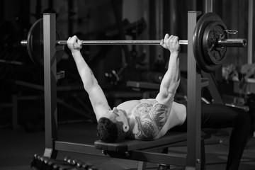 Brutal athletic man pumping up muscles on bench press, black and white