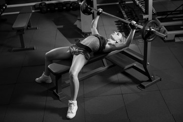 Sports young woman doing exercises with barbell on bench in the gym. Bar Bench Press. black and white