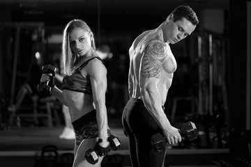 Beautiful young sporty sexy couple showing muscle and workout in gym. black and white