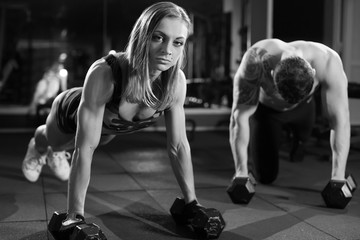 Gym man and woman push-up strength pushup with dumbbell in a fitness workout. black and white