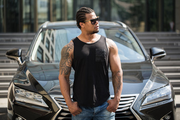 Black man in sunglasses standing near the car with modern building on background