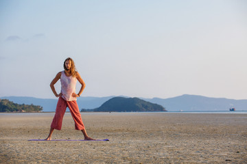 Man is doing yoga on the beach