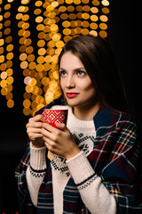 Beautiful woman enjoying a cup of hot tea in the winter time