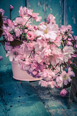 Romantic Spring background with a vase of Japanese cherry blossoms on wooden table