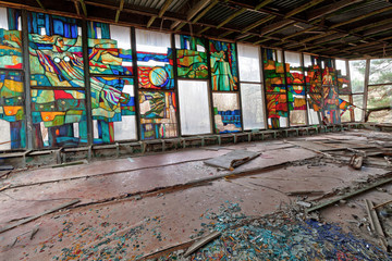 Stained glass inside of abandoned and ruined building of river port in overgrown ghost city Pripyat.