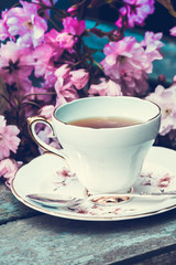 Beautiful, vintage teacup with Japanese cherry tree blossoms, shot from above.