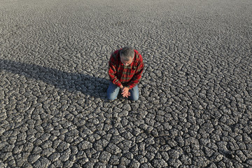 Desperate man kneeling and praying at dry cracked land after drought, natural disaster
