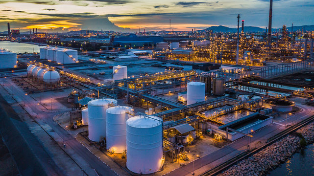 Aerial view oil terminal is industrial facility at night for storage of oil and petrochemical products ready for transport to further storage facilities in city skyline.