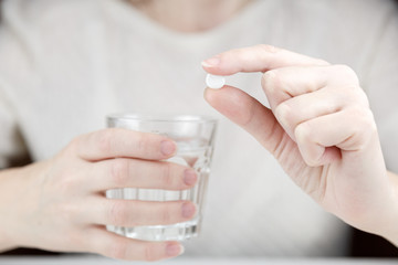 сlose-up view photo of female hands holding one white round pill and glass of water. Young woman taking medication, feeling ill. Healthcare concept