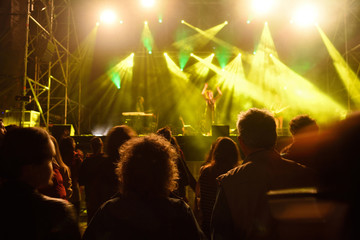 People silhouettes in front of bright stage lights.