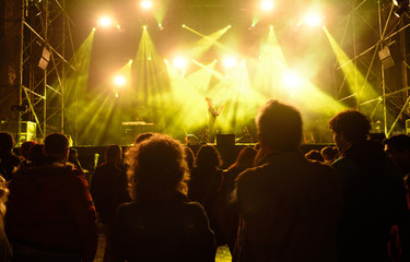 People silhouettes in front of bright stage lights,