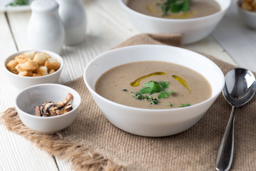Mushroom cream soup with herbs and spices over rustic wooden background