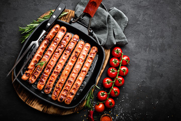 Grilled sausages bratwurst in grill frying-pan on black background. Top view. Traditional German cuisine. Stock image