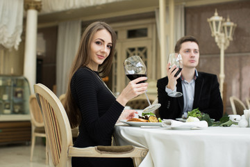 Beautiful woman and man in restaurant, holding glass of wine