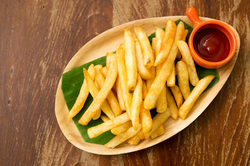 French fries with tomato ketchup on wood
