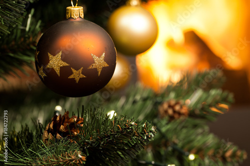 decorations on christmas tree and fire burning in fireplace in the background