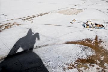 Der Schatten des Dschingis Khan Denkmals im Schnee