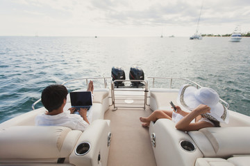 Handsome man and woman on deck of yacht with mobile phone and laptop