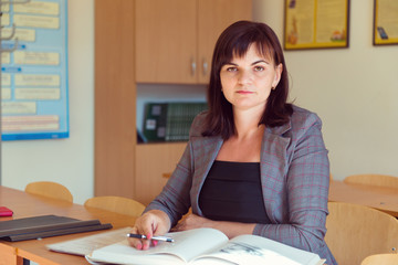 Pretty young teacher is sitting  with books  in classroom