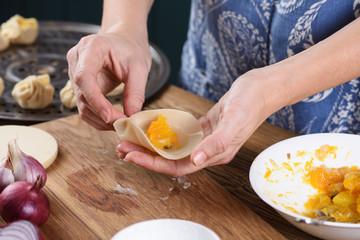 Cooking technique. Woman hands making Asian steam dumplings with pumpkin