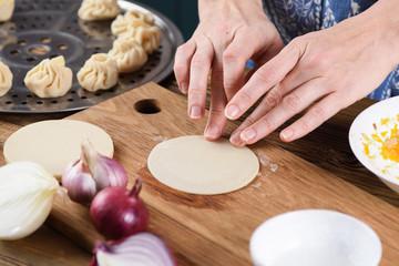 Cooking healthy vegetarian dish. Woman hands making steam dumplings momo