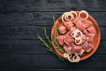 Raw uncooked meat sliced in cubes on wooden rustic background, top view.