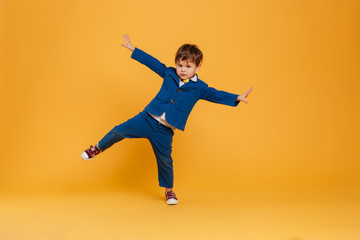 Funny little boy child standing isolated over yellow