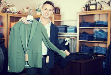 Smiling male customer choosing new jacket