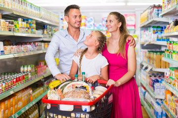 Attractive woman and man with teenager girl in the shop