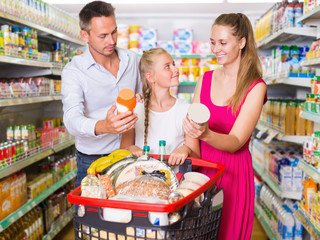 Parents with girl standing with purchases in shopping cart