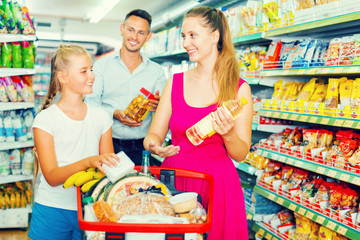 Positive family with teen daughter and purchases in shopping