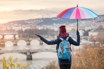 Girl walking with umbrella on rainy day in historical center of Prague, Europe