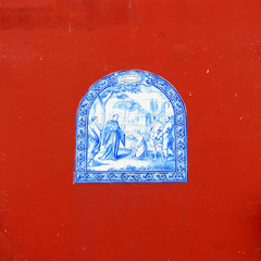 Portuguese religious tile on a red wall