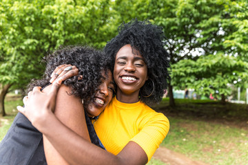 Afro friends hugging in the park