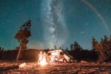 Vanlife couple standing in front of campfire and van under Milky Way night sky.