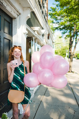 A teenage girl holding balloons walking down a city street