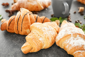 Delicious sweet croissants on table